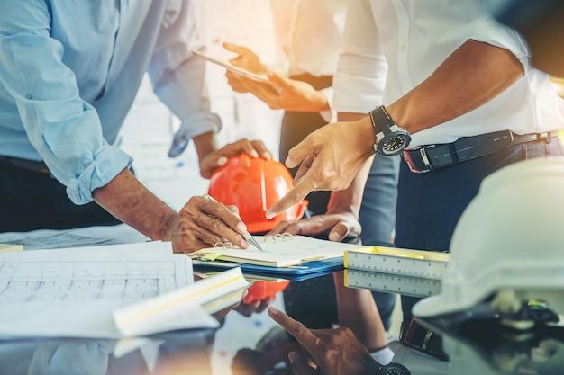 Contratista e ingeniero con planos discuten en un sitio de construcción moderno, ingenieros en instrucciones de lectura de fábrica mecánica Foto Premium