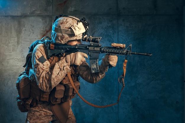 Contratista militar privado estadounidense disparando un rifle, foto de estudio Foto Premium