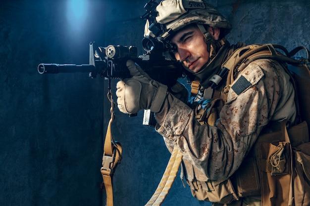 Contratista militar privado estadounidense disparando un rifle. tiro del estudio Foto Premium