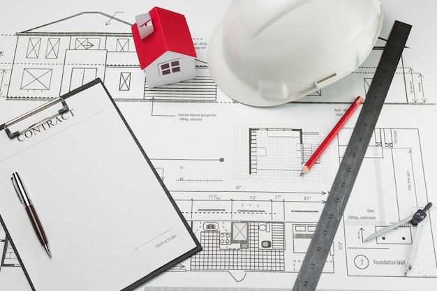 Contrato de papel y modelo de casa con casco blanco en plano Foto gratis