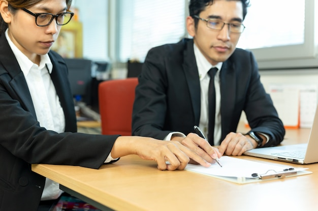 Contratos de firma del ejecutivo de operaciones con la secretaria en el escritorio en oficina. Foto Premium