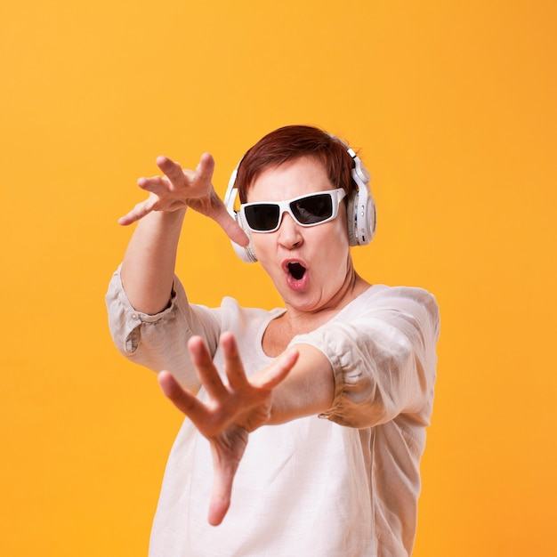 Cool senior mujer escuchando música y bailando Foto gratis