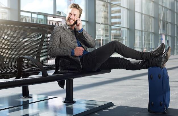 Cool travel man relajante en el aeropuerto con teléfono móvil Foto Premium