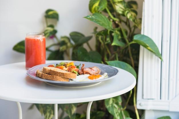 Copa de batido; desayuno en plato sobre la mesa redonda blanca. Foto gratis