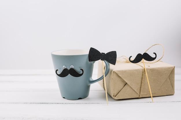 Copa con bigote ornamental cerca de caja y pajarita en varita Foto gratis