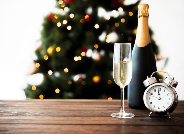 Copa de champagne con botella en mesa Foto gratis