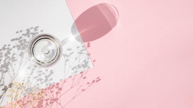 Copa de champán con un blanco en blanco sobre un fondo rosa con sombra de rama Foto gratis