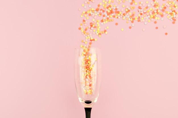 Copa de champán llena de purpurina Foto gratis