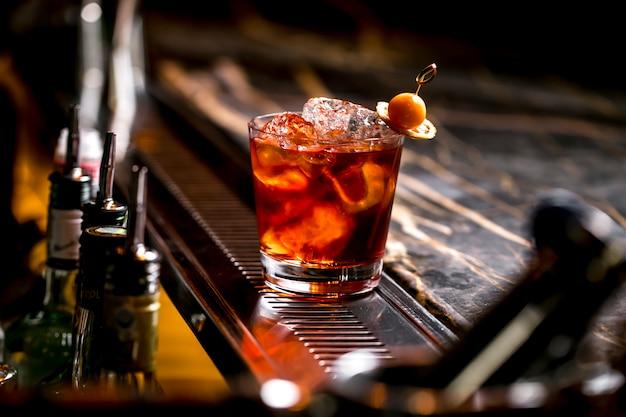 Una copa de cóctel con cubitos de hielo con limón seco y fruta. Foto gratis