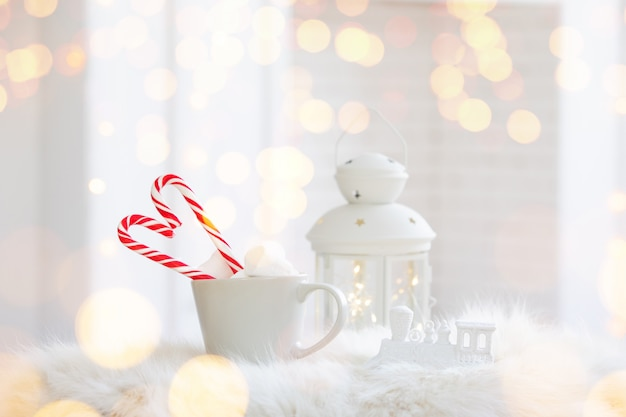 Copa de invierno de bebida caliente con un bastón de caramelo sobre fondo blanco de madera Foto gratis