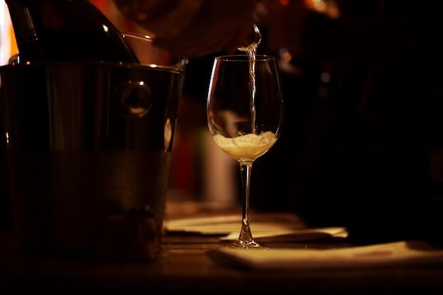 La copa de vino iluminada está sobre la mesa y se vierte un poco de champán rosado. Foto Premium
