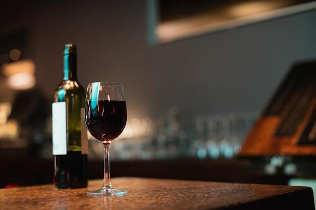 Copa de vino tinto y botella en barra de bar Foto gratis