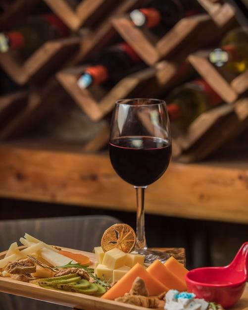 Copa de vino tinto servido con plato de queso Foto gratis
