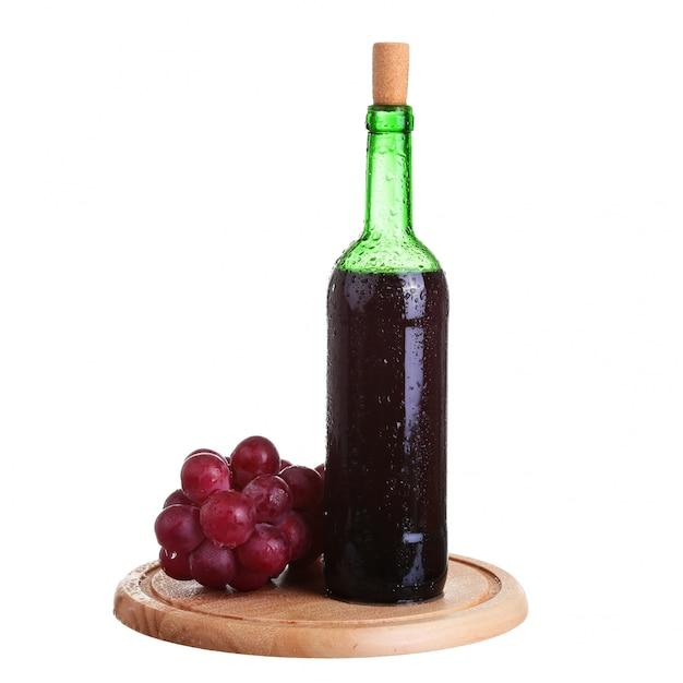 Copa de vino con vino tinto, botella de vino y uvas aisladas sobre fondo blanco. Foto Premium