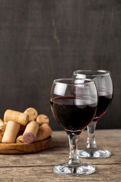 Copas de ángulo alto con vino tinto en la mesa Foto gratis