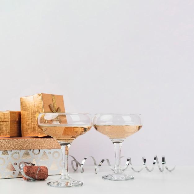 Copas de cóctel con regalos en la mesa Foto gratis
