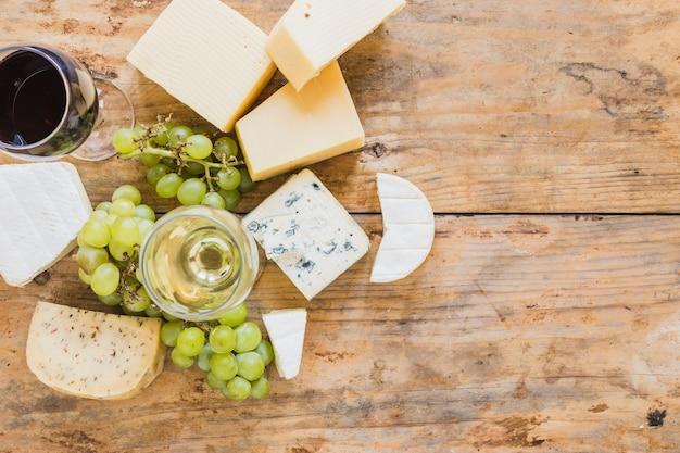 Copas de vino con uvas y variedad de bloques de queso en el escritorio de madera Foto gratis