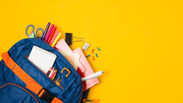 Copia amarilla con mochila llena de útiles escolares. Foto Premium