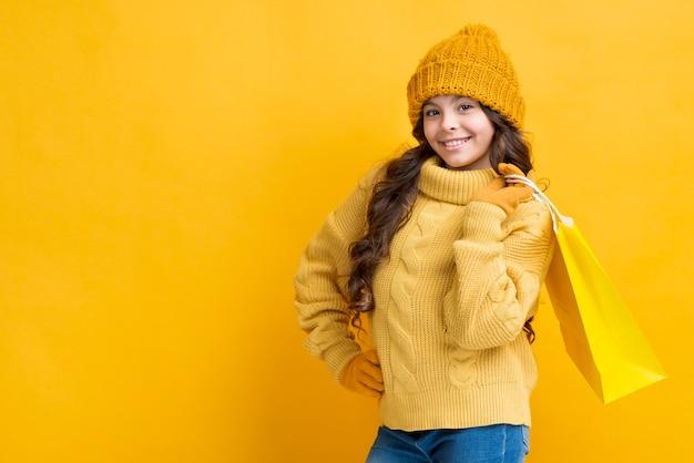 Copia espacio chica con bolsa de ropa de compras de invierno Foto gratis