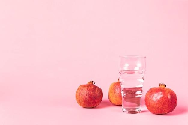 Copia espacio fondo rosa con fruta de granada Foto gratis