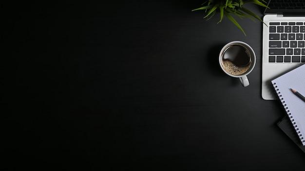 Copia espacio mesa de oficina negro con laptop, cuaderno, lápiz y taza de café con plat. Foto Premium