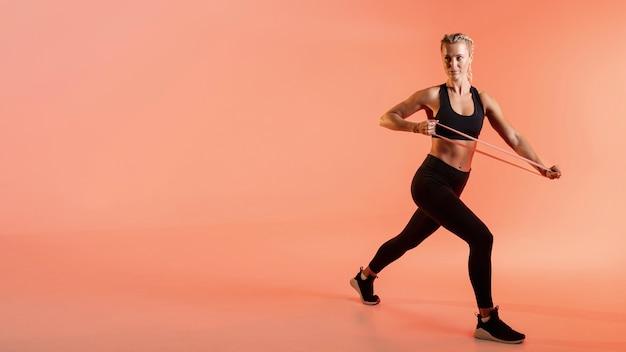 Copia espacio mujer entrenando con banda elástica Foto gratis