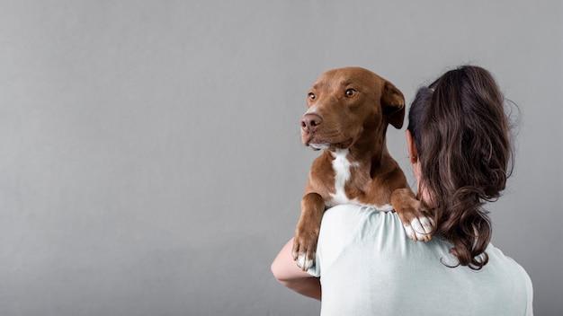 Copia-espacio mujer sosteniendo perro Foto gratis