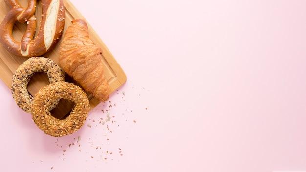 Copia-espacio tablero de madera con pretzel y croissant Foto gratis