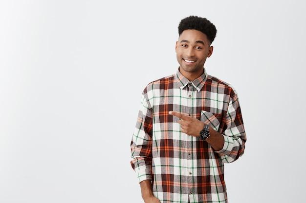 Copiar espacio para publicidad. de piel oscura joven apuesto hombre alegre con peinado rizado en camisa a cuadros apuntando a un lado con una mano con sonrisa y expresión feliz. Foto gratis