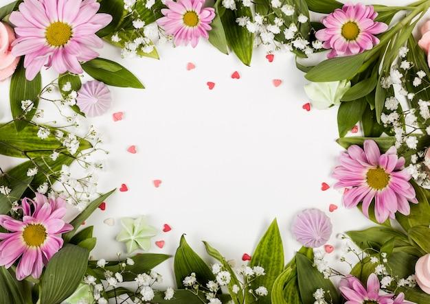 Copie el espacio rodeado de flores y hojas rosas Foto gratis