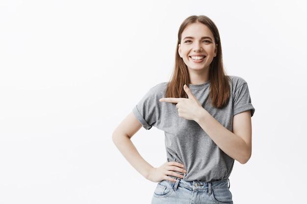 Copie espacio para su anuncio. joven hermosa caucásica chica morena sonriendo, con expresión feliz, apuntando un lado con el dedo en la pared blanca. Foto gratis
