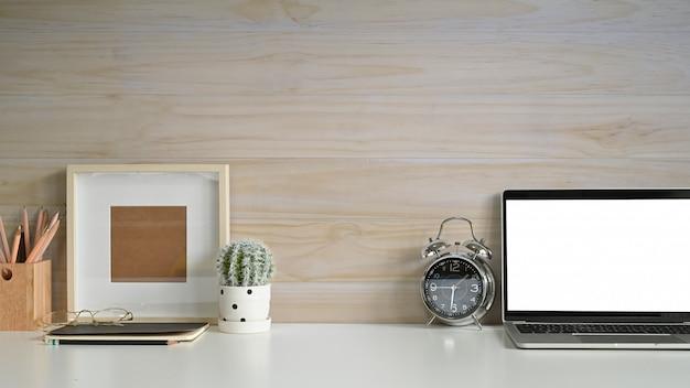 Copie el espacio de trabajo portátil maqueta portátil, marco de fotos, reloj despertador y cactus en el escritorio con pared de madera. Foto Premium