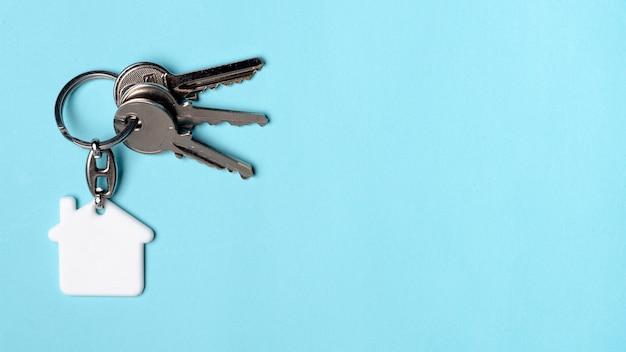 Copie el fondo del espacio azul con las llaves de la casa Foto gratis