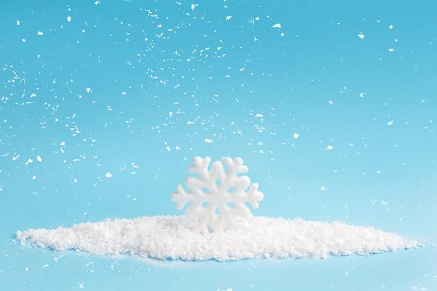 Copo de nieve y nieve sobre fondo azul. composición navideña. Foto Premium