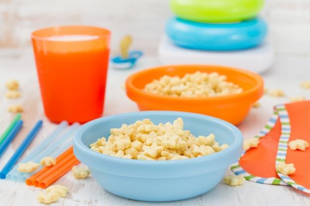 Copos de maíz en un tazón azul con leche en madera blanca Foto Premium