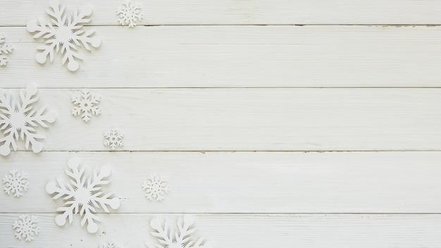 Copos de nieve decorativos de navidad laicos planos sobre tabla de madera Foto gratis