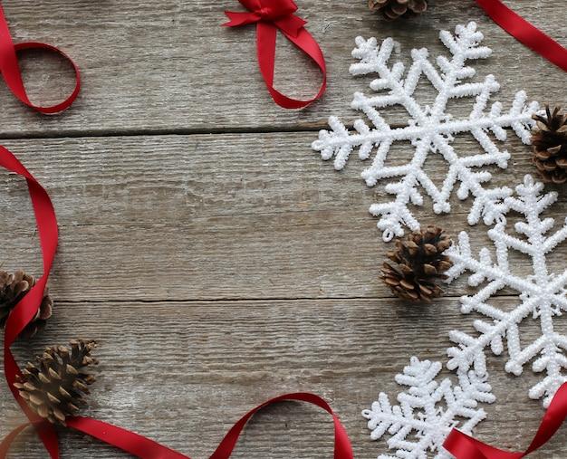 Copos de nieve, piñas y cintas rojas. Foto gratis