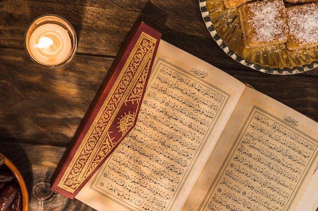 Corán cerca de la vela y el postre Foto gratis