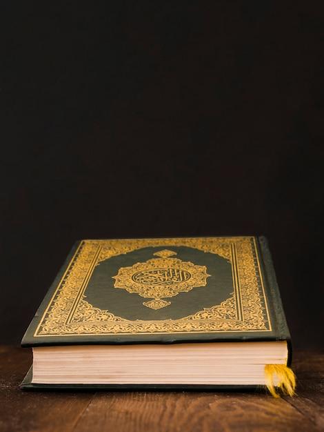 Corán cerrado sobre una mesa con fondo negro Foto gratis