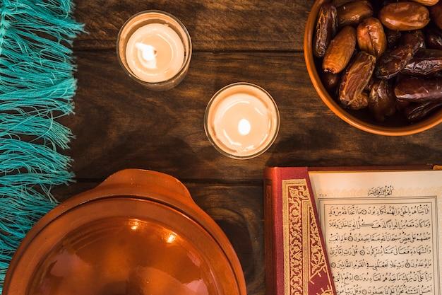 Corán y fechas cerca de velas encendidas Foto gratis
