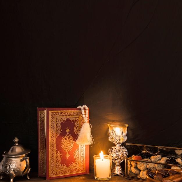 Corán y velas cerca del dulce Foto gratis