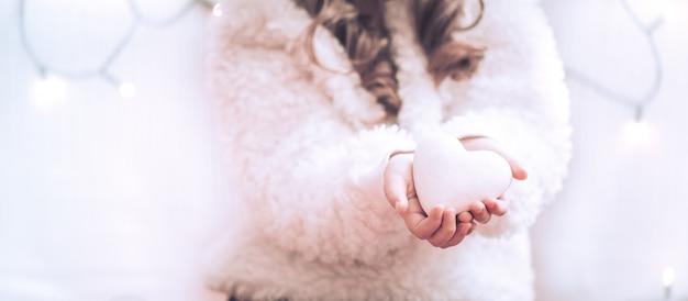 Corazón blanco en manos de una niña Foto gratis