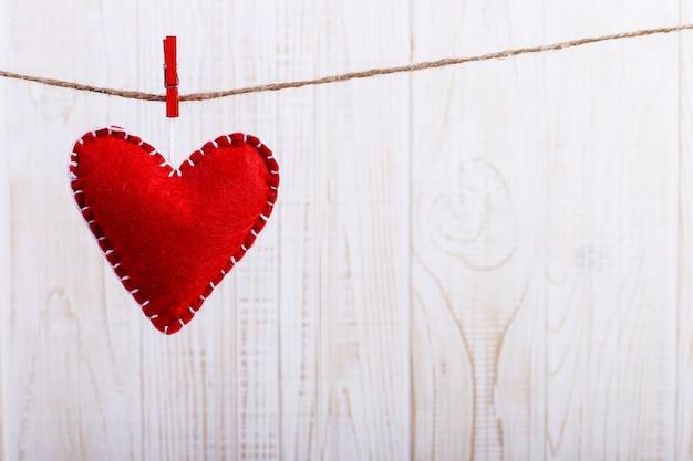 Corazón de fieltro rojo sobre una cuerda, sobre fondo blanco de madera Foto Premium