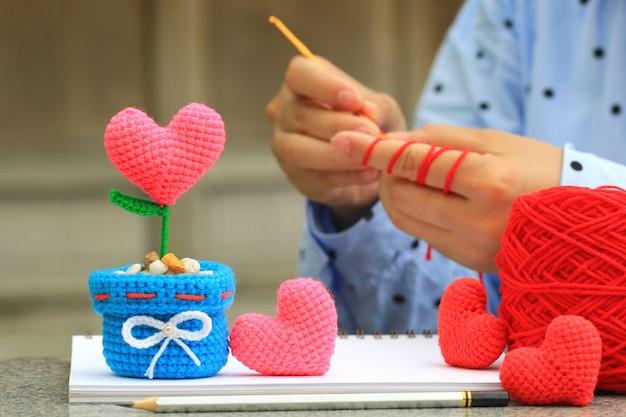Corazón de ganchillo hecho a mano y mujer con su ganchillo, día de san valentín Foto Premium