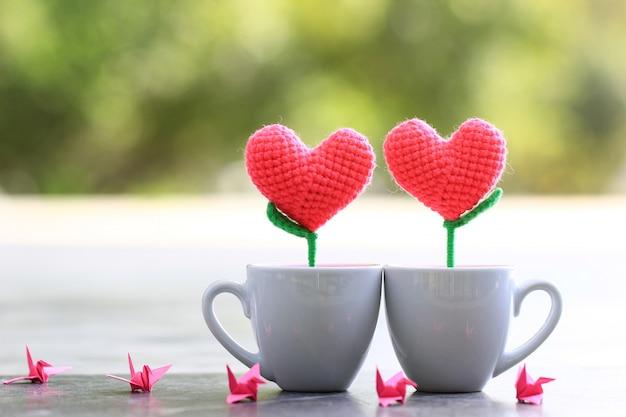 Corazón de ganchillo hecho a mano en la taza blanca para el día de san valentín Foto Premium