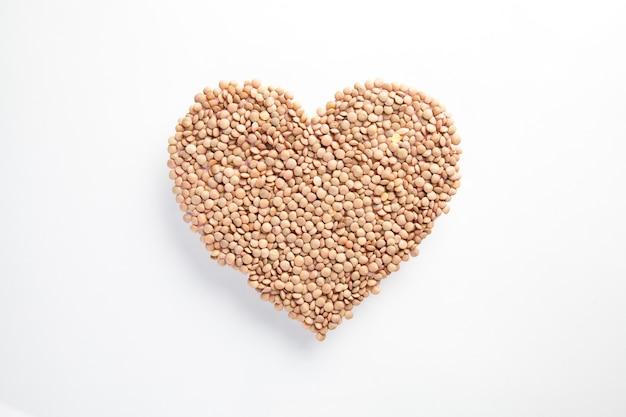 Corazón de lentejas crudas sobre pared blanca, concepto de vida sana y  nutrición   Foto Premium