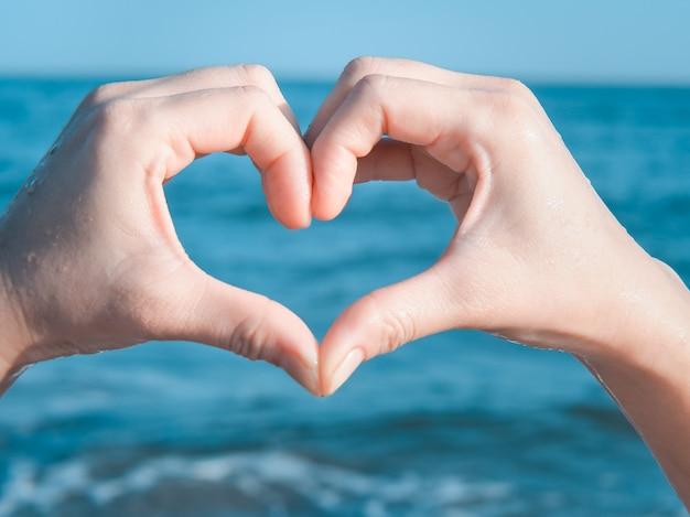 Corazón de manos en la playa | Foto Premium