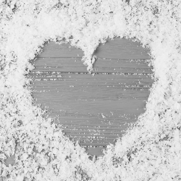 Corazón entre nieve decorativa en escritorio de madera Foto gratis