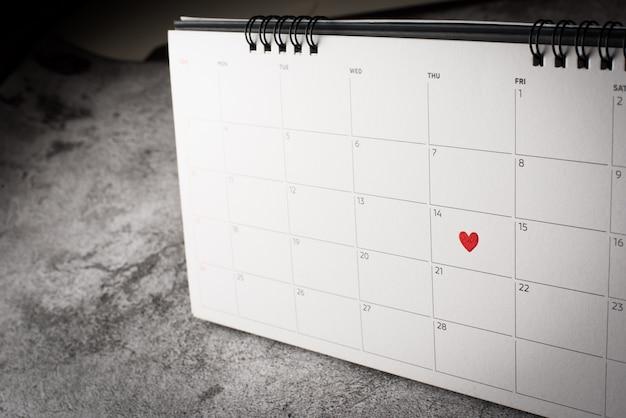 Corazón rojo el 14 de febrero en el calendario, concepto de día de san valentín. Foto gratis
