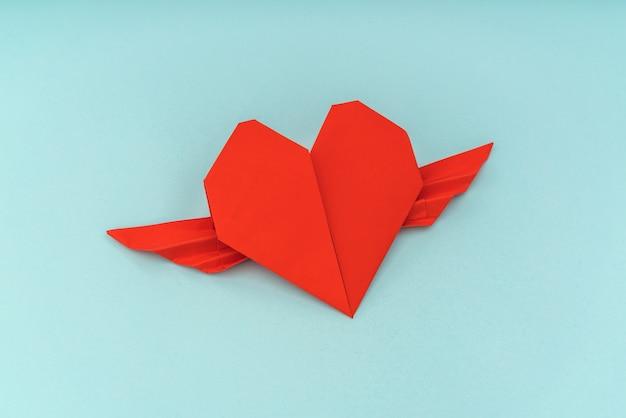 Corazón rojo del origami de papel con alas sobre fondo azul ...